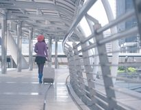 Back view woman traveler walking with suitcase at airport corridor royalty free stock photography