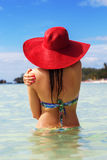 Back view of woman in tropical paradise. Back view of fashion woman is swimming on the beach and wearing red hat, summer vacations Royalty Free Stock Images
