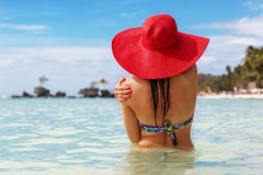 Back view of woman in tropical paradise. Back view of fashion woman is swimming on the beach and wearing red hat, summer vacations in Philippines Royalty Free Stock Images