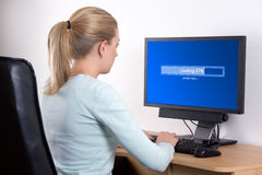 Back view of woman using personal computer in office Stock Images