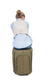 Back view of woman  in vest sits on a suitcase. Stock Photo