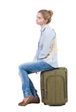 Back view of woman  in vest sits on a suitcase. Royalty Free Stock Image