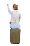 Back view of woman  in vest sits on a suitcase and pointing. Stock Images