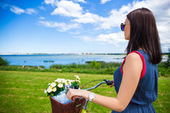 Back view of woman with vintage bicycle and flowers in wicker ba Royalty Free Stock Image