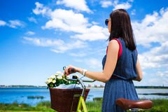 Back view of woman with vintage bicycle and flowers in wicker ba Royalty Free Stock Photos