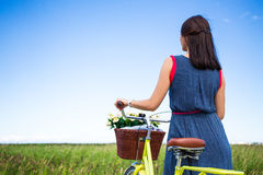 Back view of woman with vintage bicycle and flowers Royalty Free Stock Image