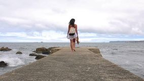 Back view of woman walking along of sea pier stock footage