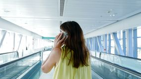 Back view, woman walking between automatic walkways, in subway crossing, talking, using her phone, a mean of. Communication, gadget. The concept is always in stock footage