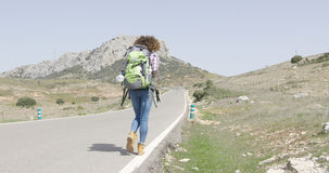 Back view of woman walking down road Stock Photos