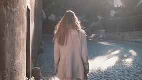 Back view of woman walking at sunny spring city street in Europe. Stylish girl exploring the old town alone. Back view of brunette woman walking at sunny spring stock footage