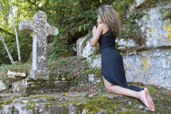Back view of a woman who is praying. Back view of a young woman who is kneeling in front of a stone cross. She is praying Royalty Free Stock Photography
