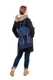 Back view woman in winter jacket  with a backpack looking up Royalty Free Stock Photos