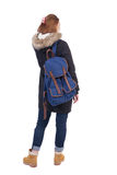 Back view woman in winter jacket  with a backpack looking up Stock Photography