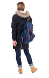Back view woman in winter jacket  with a backpack looking up Royalty Free Stock Photo