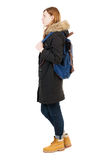 Back view woman in winter jacket with  backpack. Back view woman in winter jacket with a backpack  looking up.   Standing young girl in parka. Rear view people Royalty Free Stock Images