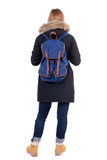 Back view woman in winter jacket  with a backpack looking up Stock Photos