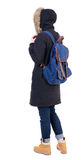 Back view woman in winter jacket  with a backpack looking up Stock Image