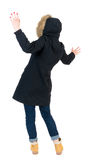 Back view woman in winter jacket Balances waving his arms. stock photo
