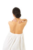 Back view woman wrapped in towel touching her back Stock Photography