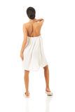 Back view woman wrapped in towel touching her neck Stock Photo