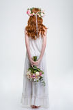 Back view of woman in wreath standing and hiding bouquet Stock Photo