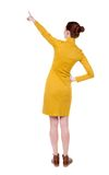 Back view of woman. Young woman in vest presses down on something. Isolated over white background. Rear view people collection. backside view of person. she Royalty Free Stock Image