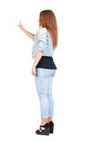 Back view of woman. Young woman in dress presses down on someth Royalty Free Stock Image