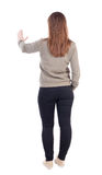 Back view of woman. Young woman presses down on something. Royalty Free Stock Photos