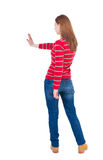 Back view of woman. Young woman presses down on something. Royalty Free Stock Image