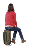 Back view of womanin cardigan sitting on a suitcase. Royalty Free Stock Photo