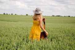 Back view of women with guitar in wide rye field Stock Photos