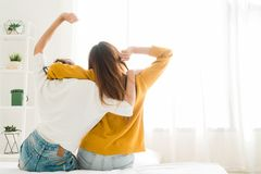 Back view of women lesbian happy couple waking up in morning, sitting on bed, stretching in cozy bedroom, looking through window. Funny women after wakeup Royalty Free Stock Photo
