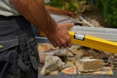 Back view of worker holding a Spirit Level and a straightedge in hand. Carpenter holding a Spirit Level and a straightedge in hand royalty free stock photos