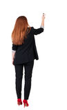 Back view of writing beautiful redhead business woman. Royalty Free Stock Photo