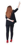 Back view of writing beautiful redhead business woman. Royalty Free Stock Photos
