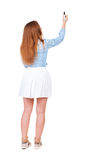 Back view of writing beautiful redhead woman. Young girl in dres Stock Photo