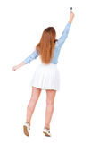 Back view of writing beautiful redhead woman. Young girl in dress draws. Rear view people collection. backside view of person. Isolated over white background stock image
