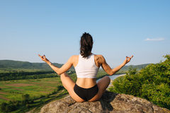 Back view of yoga woman with perfect muscular body meditating in lotus posture on the rock. Mountain landscape and blue Royalty Free Stock Photos