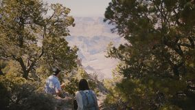 Back view young adult couple of hikers sit together eating ice cream at epic scenic view of Grand Canyon in Arizona USA. Back view young adult couple of hikers stock footage