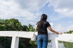 Back view of young adult woman wearing black shirt standing on old bridge and look at the sky stock photography