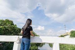 Back view of young adult woman wearing black shirt standing on old bridge and look at the sky. With copy space for text., nature concept. goal concept. decision Royalty Free Stock Image