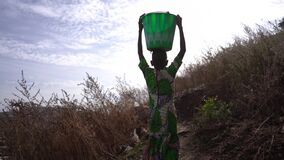 Back View Of a Young African Girl Carrying Home a Heavy Water Bucket From A Distant Village Water Place