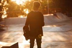 Back view of a young african male teenager with earphones. Standing and holding skateboard at skate park Stock Image