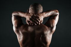 Back view of young african man with muscular body holding his ne. Ck,  on black background Stock Photos