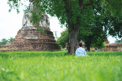 Back view. young woman be meditation on green grass field under. Back view. young asia woman be meditation on green grass field under big tree with old pagoda Royalty Free Stock Images