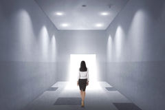 Back view of a young asian business woman walking to opened door Royalty Free Stock Image