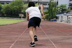 Back view of young Asian sprinter leaving starting on racetrack at athletics stadium. Back view of young Asian sprinter leaving starting on racetrack at Royalty Free Stock Image