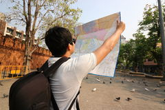 Back view of young asian tourist with backpack bag exploring a map in Tha Phae gate , Chiang Mai , Thailand . Handsome young asian tourist with backpack bag royalty free stock photos