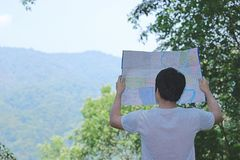 Back view of young Asian tourist exploring map among green fresh nature background. Travel and adventure concept. Back view of young Asian tourist exploring map stock image