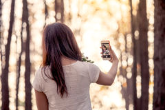 Back view of young asian woman taking selfie on mobile phone Stock Photos